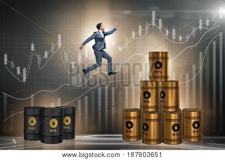 Businessman jumping from stack of oil barrels
