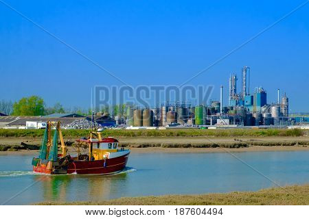 Fishing boat on the river Rother passing by a oil and gas  company near Rye, East Sussex, England, UK