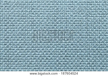 Light blue background with checkered pattern closeup. Structure of the cyan fabric macro.