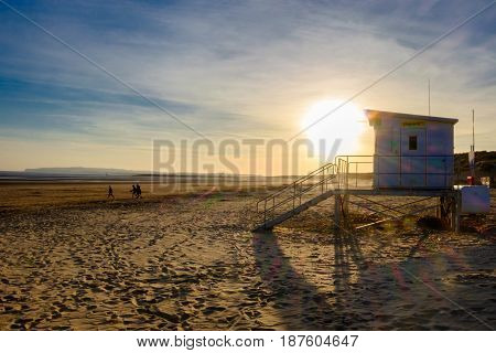 Lifeguard house at sunset in spring at low tide on Camber Sands beach, East Sussex, England, U.k