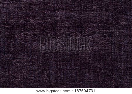 Dark purple fluffy background of soft fleecy cloth. Texture of wine fuzzy textile closeup.