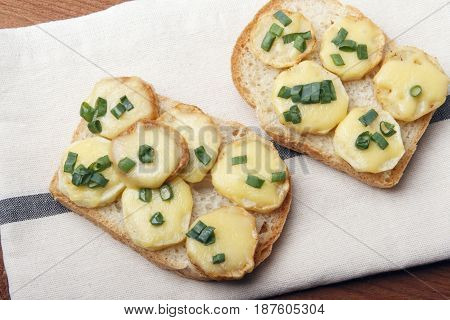 Appetizer of wheat bread potatoes cheese and green onions