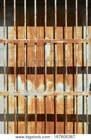 Rusty metal sheet fence with grille under sun light and shady