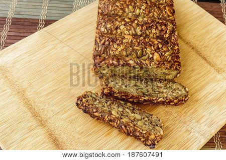 healthy seed and nut loaf on wooden cutting board