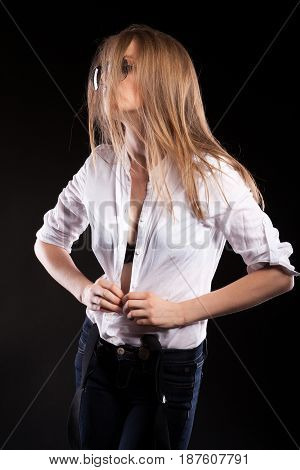 Sensual sexy woman with suspenders undresing herself on black background in studio photo