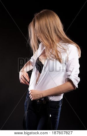 Sexy woman with suspenders undresing herself on black background in studio photo