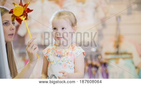 Cute girl with mother playing in the children's clothing store in front of the mirror