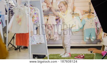 Cute little girl happy with new clothes, standing in front of a mirror in a clothing store for children
