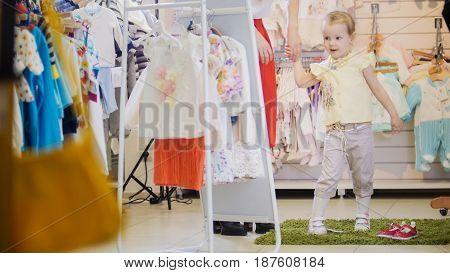 Little girl in a summer suit holding his mother's hand and looks in the mirror in the children's clothing store