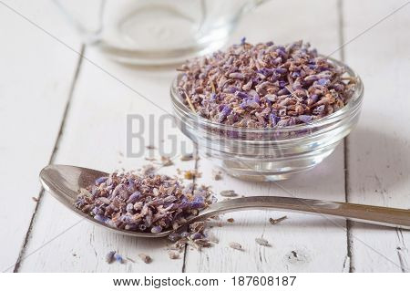 Dry lavender flowers and essential oil on white background . Aromatherapy oil in transparent bowl. Lots of dried seeds in transparent glass surrounded by dry violet flowers. Awakening the senses.