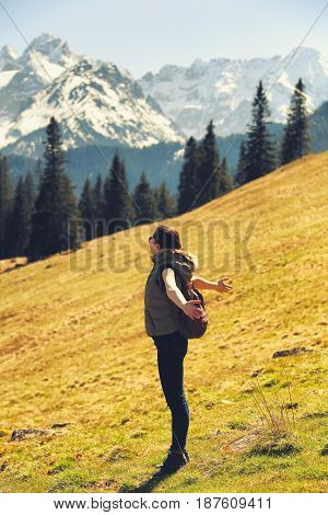 Pretty woman caught fresh air on mountain hill. One white tourist girl hiking in Alps. Summer mountain background.