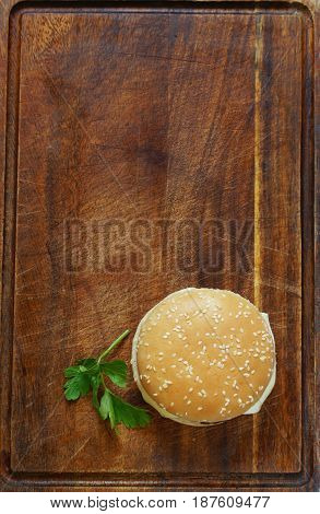 Fast food burger with french fries on a wooden board