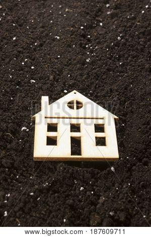 Model of a house in the background of a dug ground