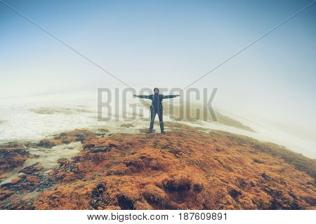 Tourist man stands in freedom pose on foggy mountain peak