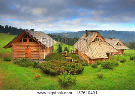 Ecological wooden houses on mounain hills. Wooden hotel on a sunny day. Beautiful place for rest. Morning landscape with green grass.