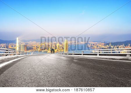 empty road with landmark buildings in hong kong at sunrise