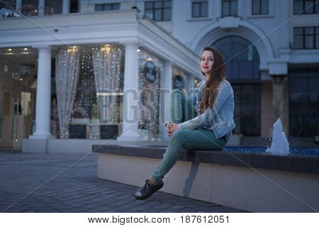 Alone beautiful girl sitting near fountain and looking at the sky and dreaming .night city life. She is waiting for somebody