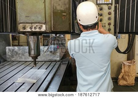 The CNC machine operator operate the old double column CNC machine with safety hat. CNC machine operation concept