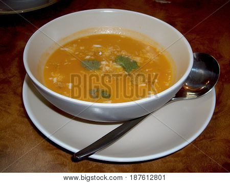 Appetizer soup in a white bowl Appetizer soup with herbs in a white bowl and spoon