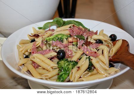 Penne pasta with bacon strips on round white plate cooked penne pasta garnished with bacon strips, cauliflower and olives in white plate