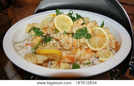 Fish fillet with slices of lemon and herbs Bite size fish fillet adorned with slices of lemon and herbs served on a white round bowl