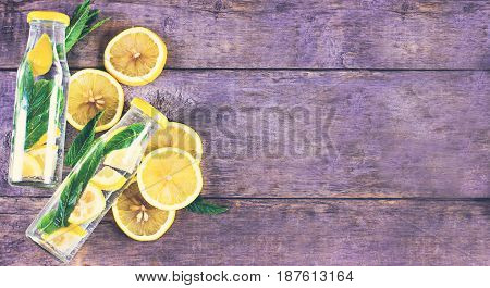 Water Bottle With Lemon And Mint On A Wooden Table.