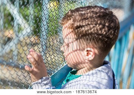 The boy stands near the metal fence .