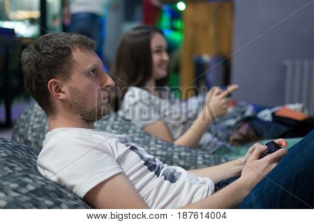Portrait of happy couple friends playing video games with joystick sitting on Bean bag chair
