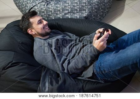 Portrait of happy gamer playing video games with joystick sitting on Bean bag chair.