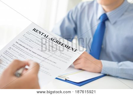 A man reading rental agreement document about to fill and sign