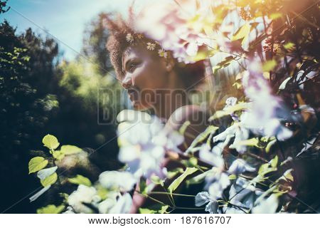 True tilt-shift view of young cute black female teenager with chamomile wreath on her head with curly afro hair standing in beautiful summer garden surrounded by light pink and light blue flowers