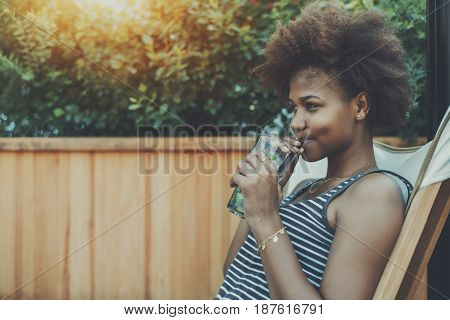 Flirty young afro american curly girl in striped t-shirt is drinking cocktail while leaning on deck chair black sexy female enjoying glass of mojito sitting in chaise-longue with copy space for text