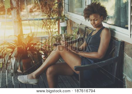 Cute brazilian lady is sitting on the veranda of tropical summer house and making selfie on her smart phone young curly afro american girl spending her morning on black bench of private cottage