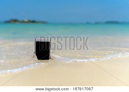 Smart phone with weather app on a sandy beach