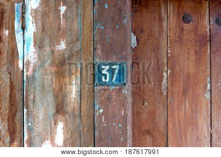 Old Metal Number 37 Plaque On A Old Wooden Door.