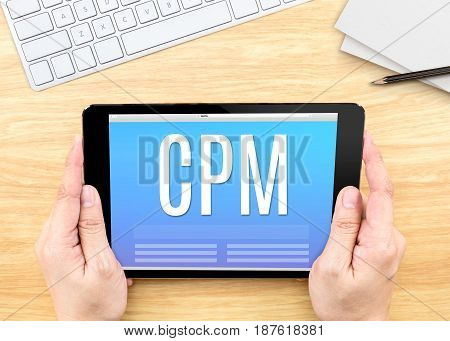 Hand Holding Tablet With Cpm (cost Per Mille)  Word On Wood Table ,internet Marketing Concept.