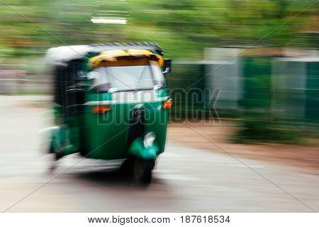 A green tuktuk (rickshaw) zooms through the street in Anuradhapura Sri Lanka.