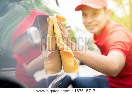 A man cleaning car with microfiber cloth - auto cleaning service concept