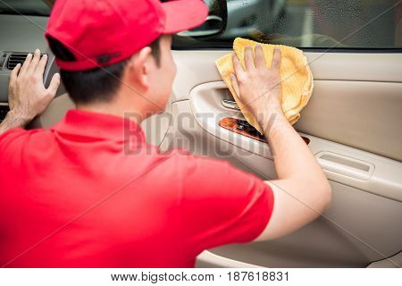 A man cleaning car door panel with microfiber cloth - auto cleaning service concept