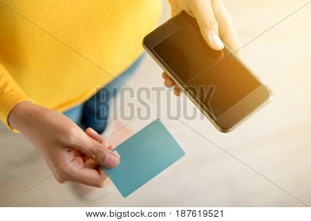 Woman hands holding smartphone and (credit) card - top view