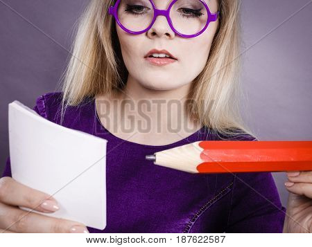 Serious student girl or female teacher business coach holding huge red pencil and note paper planning. Studio shot on grey