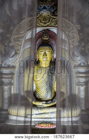 Atmospheric shot of a shrine behind curtains of one of the many sculptures of buddha inside Dambulla cave temple. Also known as the golden temple of dambulla, Sri Lanka.
