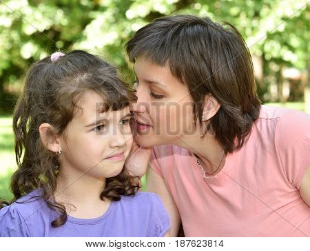 Mother whispering secret into ears of surprised daughter