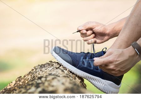 Cropped Shot Of Young Man Runner Tightening Running Shoe Laces, Getting Ready For Jogging Exercise O