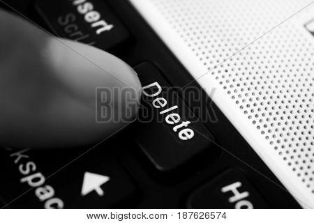 Finger hit the delete button close up.