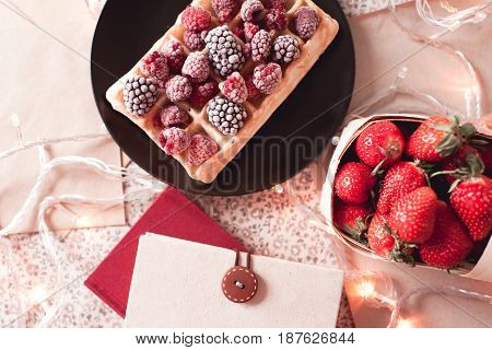 Belgian waffles with fresh fruits books and raw strawberry on table with lights. Top view. Selective focus.