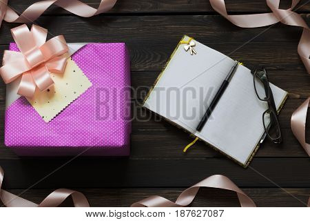 Gift box and notebook on a dark wooden background