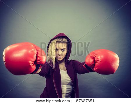 Sporty woman wearing red boxing gloves fighting. Studio shot on dark background.