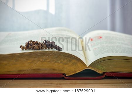 Catholic rosary beads and bible on wooden table.