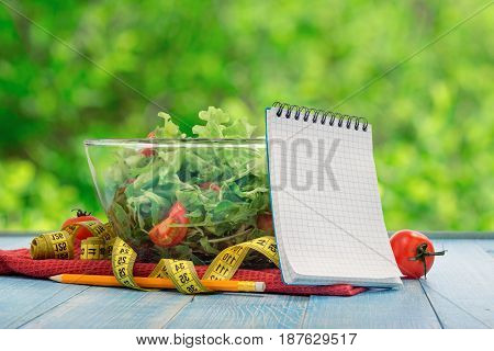 Blank notebook with large bowl of salad and measuring tape close up on blue wooden table against background of green bokeh leaves